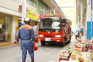 店舗外に商品などが並び、消防ポンプ車の進行に支障をきたしたユーグレナモール=9日午後