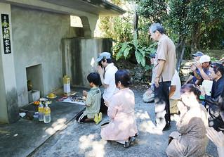 石垣喜宣氏の墓前で公演の成功を祈る関係者ら=19日午後、字石垣