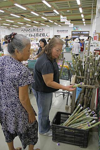 仏壇へ供えるサトウキビを品定めをする買い物客=2日午前、JAおきなわファーマーズマーケットやえやま「ゆらてぃく市場」