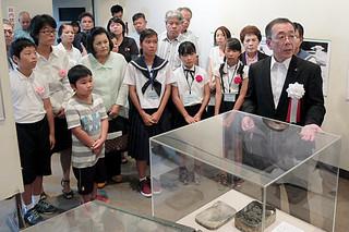 平和記念資料館の諏訪良彦副館長(右)から展示物について説明を受ける人たち=3日午前、石垣市民会館展示ホール