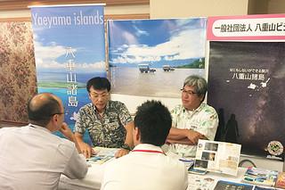 名古屋市で開かれた「OKINAWA離島コンテンツフェア2017」で八重山ブースに訪れた地元旅行担当者に離島観光をPRするYVB担当者(奥)=8日午後、中日ビル(YVB提供)