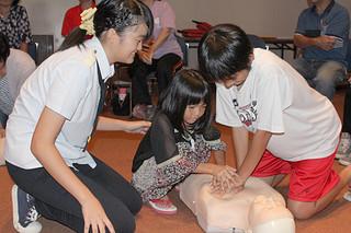 応急手当ての方法を学ぶ子どもたち=9日午後、市民会館中ホール