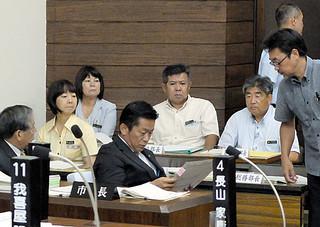 崎枝純夫氏から提出された文書の内容を確認する中山義隆市長(中)=12日午後、本会議場