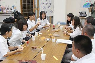 天ぷらを食べながら魚の種類などを学ぶ八重山商工高校商業科3年観光コースの生徒ら=15日午前、同校