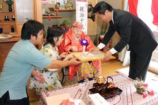 中山義隆市長から祝い状を受け取る親泊千代さん=18日午前、大川の親泊菊さん宅(千代さんの次女)