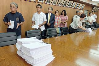 中山義隆市長に署名簿(手前)を提出した後、「市民の意思の尊重を」と訴える嶺井善共同代表(左)ら=19日午後、庁議室
