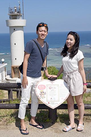 昨年7月の県内初認定を受けて設置された「恋する灯台」の看板と記念写真に納まる観光客。後ろは平久保崎灯台=19日午前、同灯台