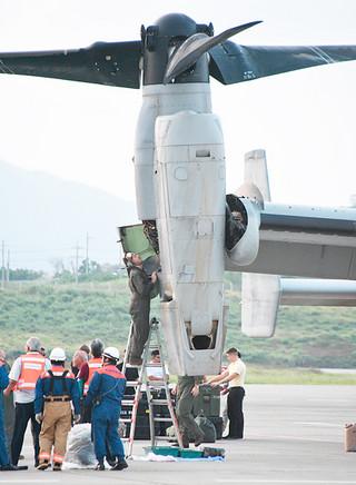 オイル漏れが確認されたオスプレイの右側エンジン。海兵隊員が点検する=29日午後6時20分ごろ、南ぬ島石垣空港
