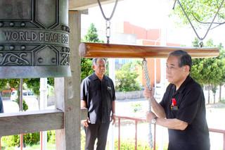 平和への祈りを込めて鐘打する参加者ら=10日正午、新栄公園