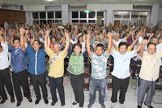 手を取り合って「頑張ろう」を三唱する支持者ら=13日夜、大川公民館