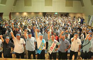 拳を突き上げて「頑張ろう」を三唱する支持者ら=15日午後、市民会館中ホール
