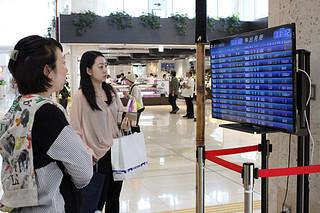 出発予定表をチェックする利用客ら=28日午前、南ぬ島石垣空港