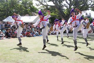 竹富島最大行事「種子取祭」の2日間の奉納芸能が幕開け。勇ましい掛け声とともに力強く跳びはねる「馬乗者(ンーマヌシャ)」に盛大な拍手が送られた=30日午前、世持御嶽