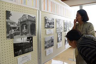 開拓移民の歴史を振り返る企画展でパネルや写真に見入る来場者=1日午前、八重山平和祈念館展示室
