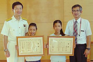 第11管区海上保安本部長賞を受賞した福里圭乃姫さん(中央左)、喜納かなんさん(同右)=8日午前、平真小学校体育館