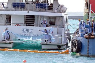 海面に流出した油を吸着シートで除去する訓練を行う参加者ら=9日午後、石垣港