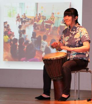特技の打楽器「ジャンベ」を披露し、振動での音の楽しみ方を伝える安里友希氏=12日午後、石垣市民会館中ホール