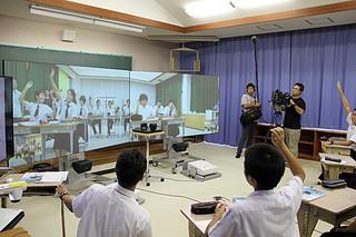 大型スクリーンを搭載したICT(情報通信技術)機器で授業を受ける与那国中(スクリーン上)と久部良中の生徒ら=14日午後、久部良中