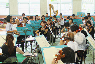 児童が振るタクトに合わせて演奏する東京シティ・フィルハーモニック管弦楽団の奏者=16日午前、海星小学校体育館