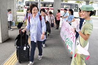 FDAのチャーター便で静岡から訪れるツアー客。ミス八重山星の砂の新嵩ひらりさん(右)から歓迎を受ける=28日午後、南ぬ島石垣空港