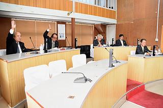 最終本会議で外間町長が提出した教育長同意の採決で挙手する与党議員(左)、賛成少数で否決となった=15日午前、町議会
