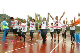 最後はチーム全員でゴールし、喜びを分かち合う参加者ら=16日午後、石垣市中央運動公園陸上競技場