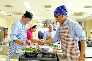 男のための料理教室」でヘルシーメニューを調理する参加者ら=15日午前、石垣市健康福祉センター2階調理室