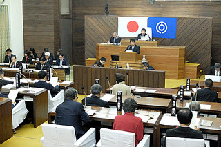 議案採決を前に各常任委員会の審査報告を受ける議員ら=18日午前、本会議場