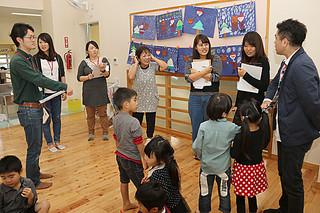 施設や保育方針について説明を受けるツアー参加者ら=22日午後、やしの実保育園