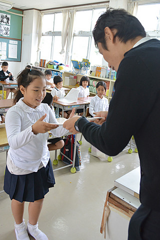 担任の水谷直揮教諭(右)から通知表を受け取る宮良小の2年生=25日午前、同校