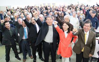 市長選に向け、「頑張ろう」をする宮良操氏(中)と支持者たち=6日夜、後援会事務所