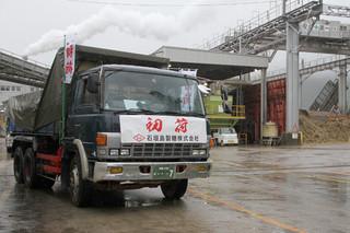 粗糖を積み込み、石垣港向け出発するトラック=7日午前、石垣島製糖