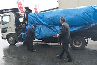 初荷の含蜜糖を満載したトラックを酒と塩で清める外間町長(右)と瑞慶覧支店長