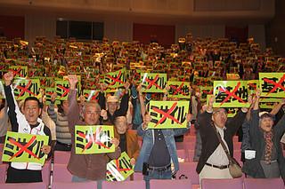 石垣市の進める反対署名の精査中止と、2018年度予算からの陸自配備関連費の撤回・削除を訴える参加者ら=18日夜、石垣市民会館大ホール