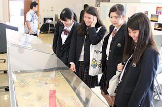石川収容所での沖縄芝居に使用された舞台衣装を見る高校生ら=20日午前、八重山平和祈念館