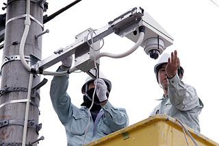 防犯カメラの取り付け作業を行う作業員=2日午後、石垣第二中学校付近