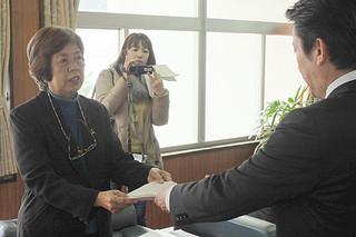 石垣市ひとり親家庭自立促進計画案を答申する山内優子委員長(左)。計画に沿った実施を要望した=8日午前、市長室