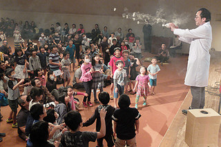 阿部清人氏が発射する煙の空気砲に大喜びの子どもたち=10日午後、市民会館中ホール
