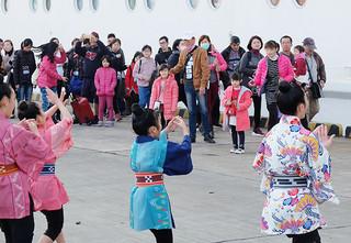 ウィングキッズリーダーズのダンスで歓迎を受ける台湾人観光客ら=12日午前、石垣港
