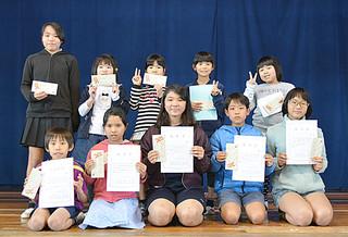 「大浜方言(ホーマムニ)発表会」に出場した皆さん。前列は入賞者。同左端は最優秀賞に輝いた3年生の前津寿也君=13日午後、大浜小体育館
