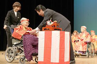 あやかりの杯の後、中山義隆市長から長寿を祝福される108歳の慶田城ヒテさん=16日午後、市民会館大ホール