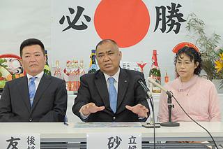三つの柱と61項目の政策を発表する砂川利勝氏(右は周子夫人、左は友利健一後援会長)=16日午前、後援会事務所