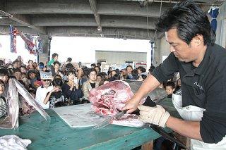 大勢の来場者らを前に、53㌔のキハダマグロを解体する八重山漁協の青年部員(右)=18日午前、八重山漁協セリ市場