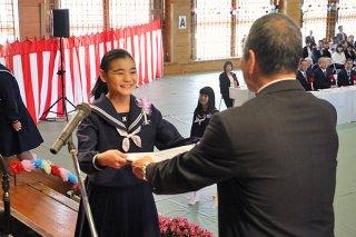 東迎和芳校長から笑顔で卒業証書を受け取る大濵珠希さん(左)=10日午前、同校体育館