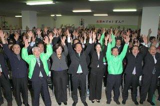 当選確実を受け、万歳で3期目の喜びを表す中山義隆氏(中央)と支持者=11日夜、選対本部