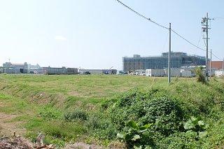新庁舎建設が予定されている旧石垣空港跡地。右奥は建設中の新県立八重山病院=18日午前