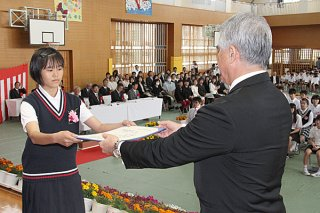 新川小学校の卒業式で、佐事安弘校長から卒業証書を受け取る卒業生(左)=22日午前、同校体育館