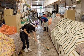 指定管理初日、半地下1階床の洗浄を行う市特産品振興協同組合のメンバーら=1日午前、石垣市公設市場