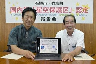 IDAからデータで送られた星空保護区の認定証を手に笑顔を見せる中山義隆市長(左)と西大舛髙旬竹富町長=3日午後、市役所庁議室