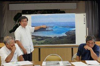 川平湾の写真を使い、高級リゾートホテルが計画されている場所を示す高嶺善伸館長=6日午後、川平公民館